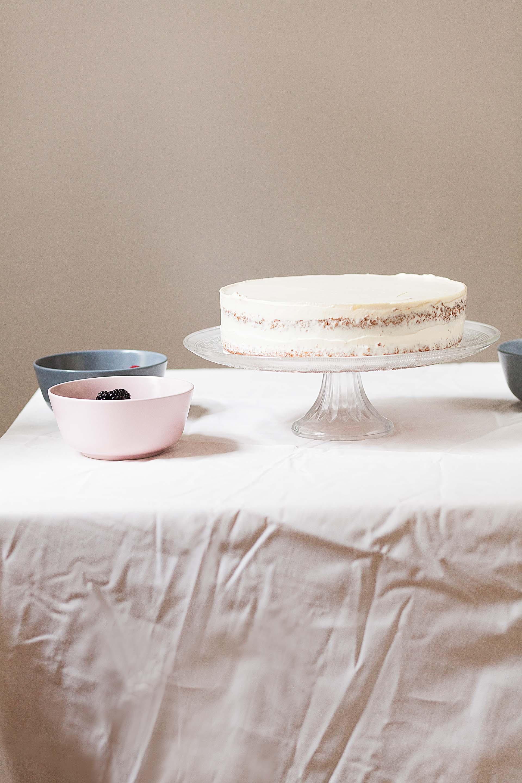 Weiße Torte auf einem Tisch mit weißer Tischdecke und eine Schüssel Himbeeren